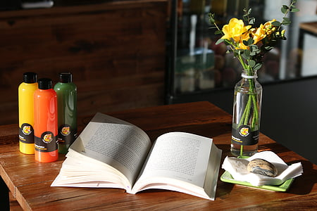 open book on top of table beside flower vase with yellow roses