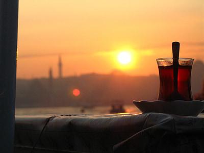 Turkish tea glass on top of saucer facing golden hour