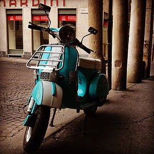 teal and white motor scooter parking near building at daytime