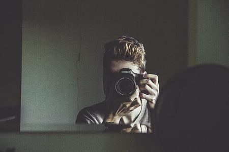 man taking photo of mirror