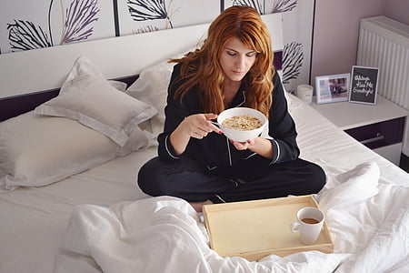 woman on bed eating cup of noodle