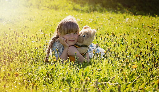 girl lying on green grass field while holding her plush toy
