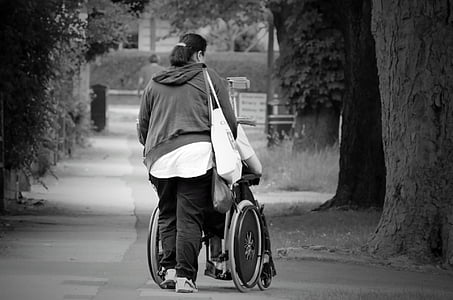 grayscale photography of woman pushing wheelchair