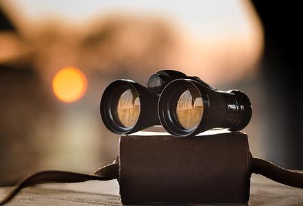 black binoculars on beige surface