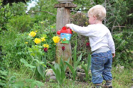 boy holding red plastic watering can