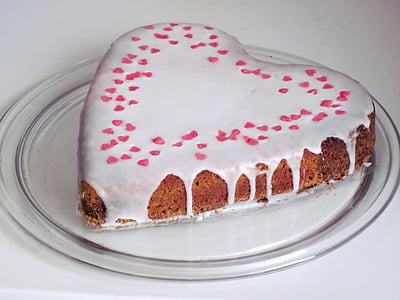 heart-shaped milk coated cake on top of clear glass plate