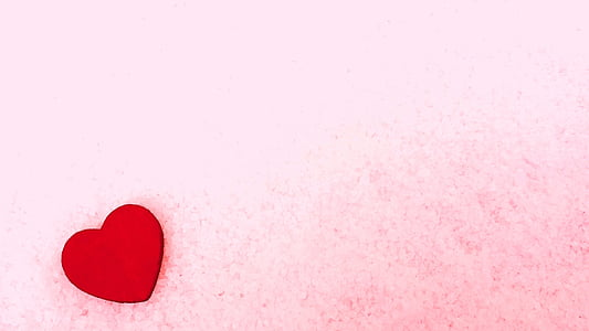 red heart wooden decor on pink sheet