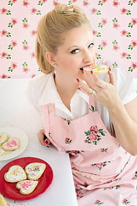 woman in pink floral apron eating cookies