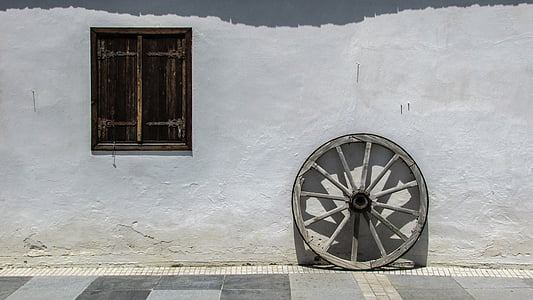 gray wooden wheel beside wall at daytime