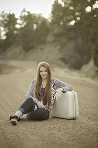 woman sitting beside luggage