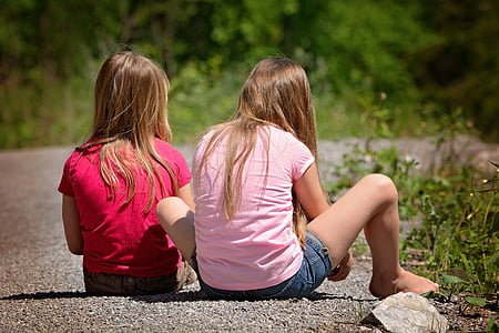 two blonde haired girls sitting on pebbled surface