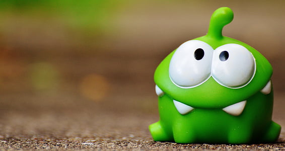 green cut the rope frog toy on brown surface