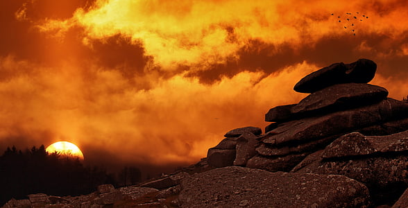 rock under cloudy sky during sunset