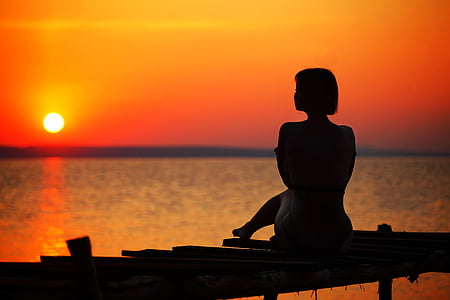 silhouette of woman sitting on dock during golden hour