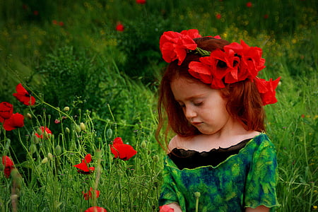 girl wearing black top standing beside red flowers