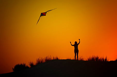 silhouette of woman flying kite