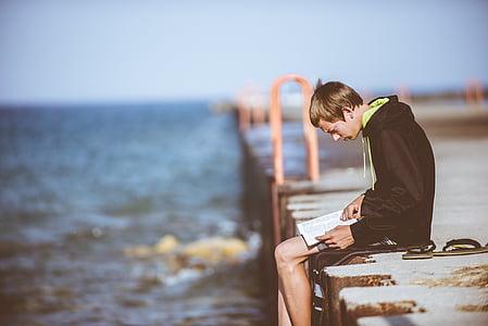 man wearing black pullover hoodie sitting near body of water during daytime