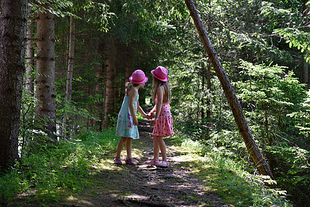 girls in pink and blue sleeveless dress holding hands