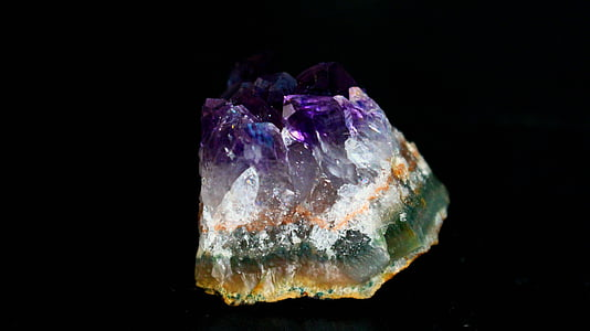 green, white, and purple stone with black background