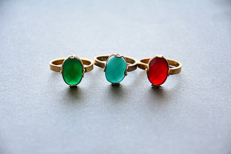 three gold-colored rings with three assorted-color gemstones