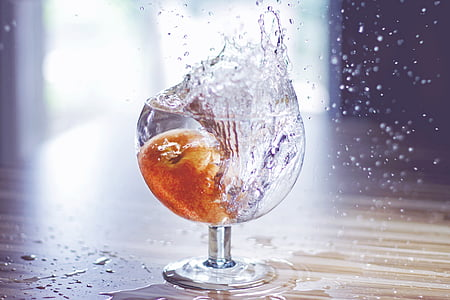 fruit drop on water filled drinking glass spilling water on brown surface