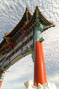 low angle photo of orange and green gate under white clouds