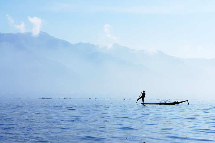 silhouette photography of person on canoe holding oar