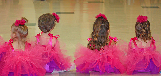 photo of four girls wearing pink ball gowns