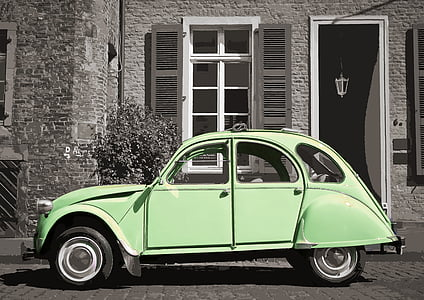 green Volkswagen Beetle parked near white painted wall and black wooden door