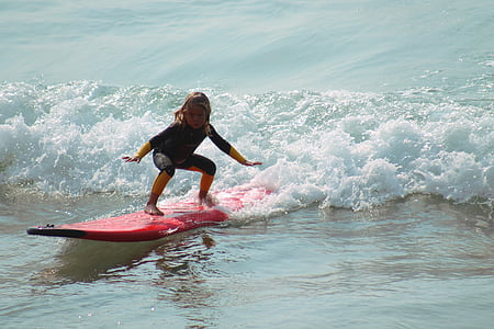 girl riding red surfboard in the ocean during daytime
