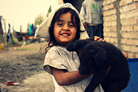 girl carrying black Labrador retriever puppy