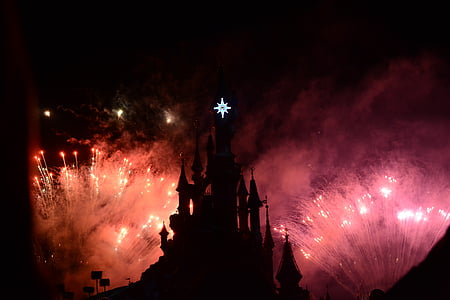 silhouette castle with lighted fireworks at night