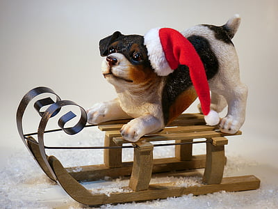 white and black ceramic dog on brown snow sled table decor on white top