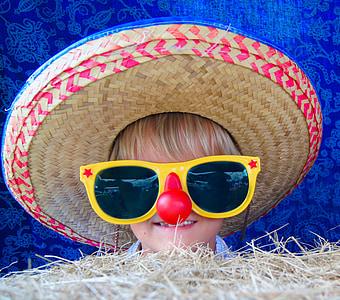 child wearing brown sombrero and yellow sunglasses