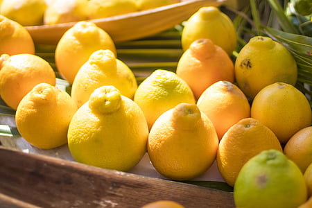 yellow lemons on brown wooden surface