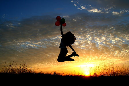 photo of woman jumping on air during golden hour