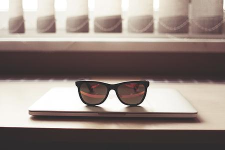 black sunglasses on top of MacBook