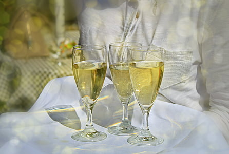 photo of three champagne glasses with champagne on white table cloth