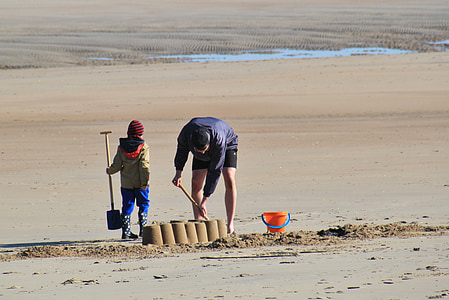 man and child making sand castles during daytime