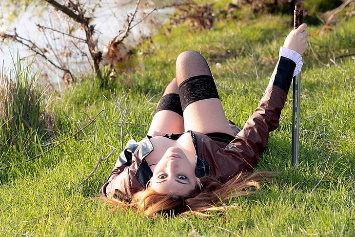 woman lying on grass near body of water