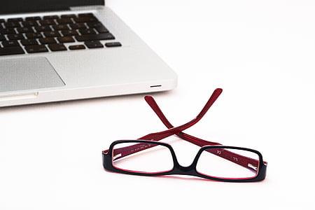 red and black framed eyeglasses beside MAcBook