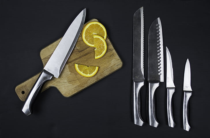 five stainless steel knives and sliced of orange fruit