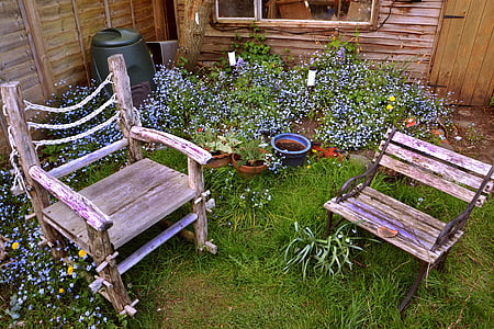 two brown wooden armchairs on garden