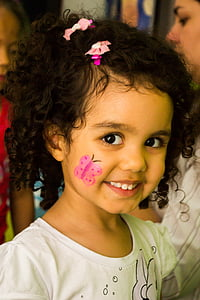 girl wearing white shirt with pink butterfly right cheek face paint