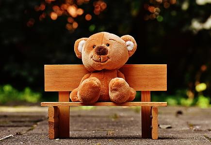 brown bear plush toy sitting on bench