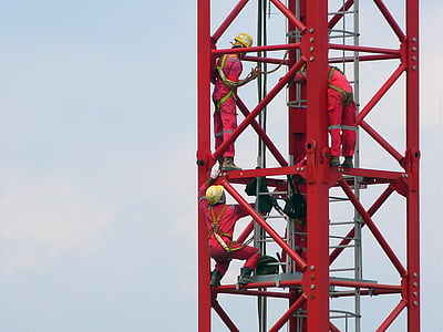 three people in red coveralls on top of tower