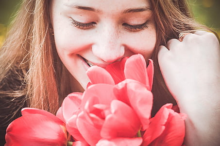 woman smelling red flowers