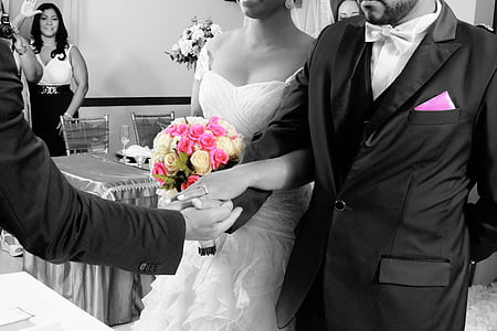 selective color photography of bride and groom holding white and pink rose flowers bouquet
