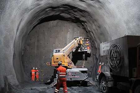 yellow and gray heavy equipment with lift in gray cave