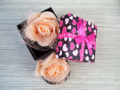 two peach-colored roses on black box